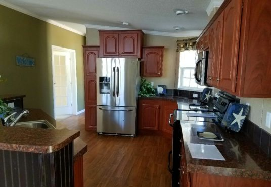 The Islander model kitchen with upgraded appliances and wood cabinets