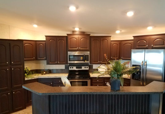 The Miley Plus model kitchen with updated appliances and wooden cabinets